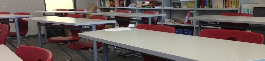 A photo of empty tables and chairs in a classroom.