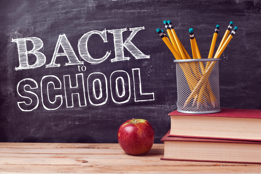 Back to school written on the chalk board, with pencils and an apple on the desk.
